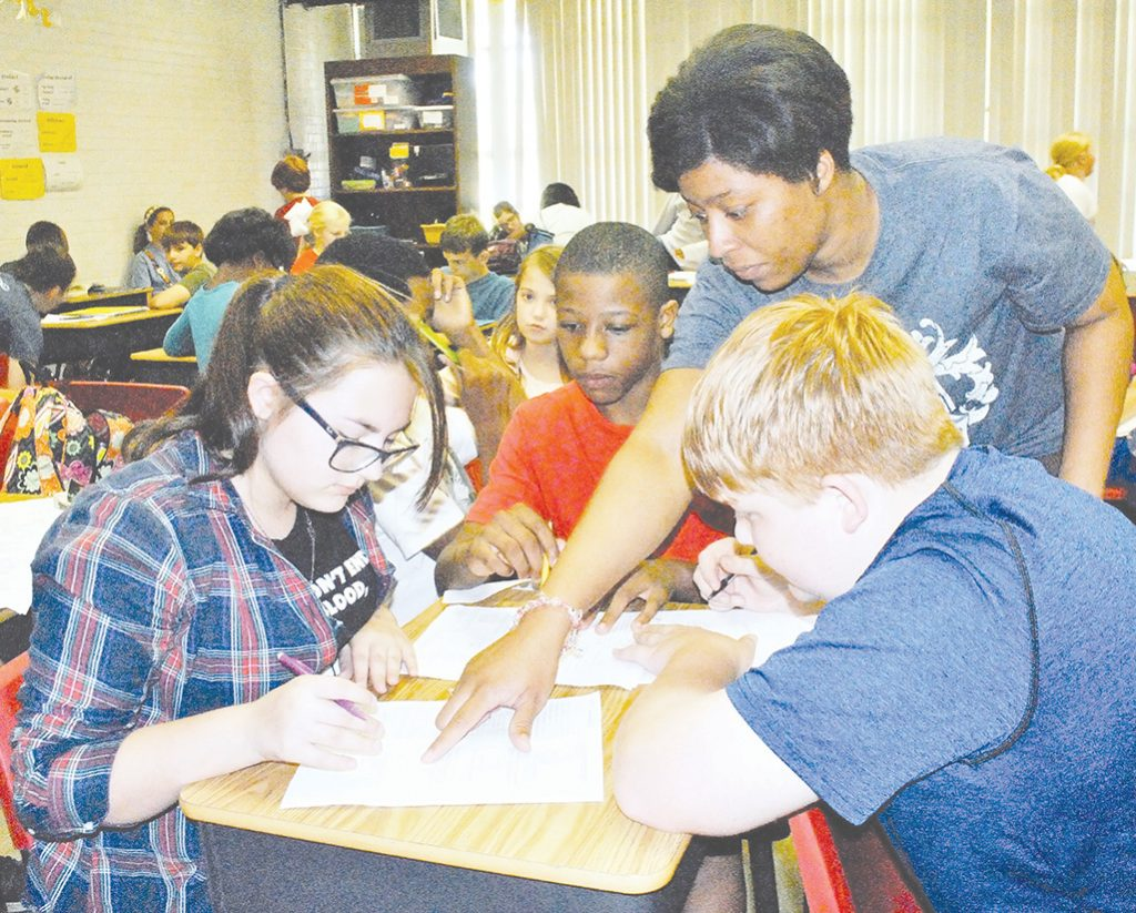 Photo by Aaron Paden/Sixth grade math teacher Shunta Davis helps a group of students with a decimals math project Thursday.