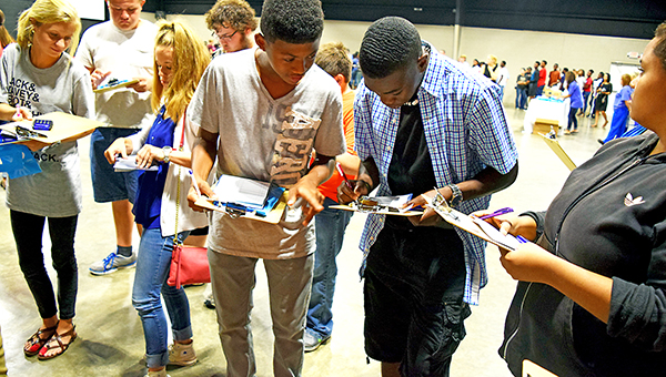 Photos by Julia Miller / Kwaman McClendon, left, and Ladarius May help each other balance their checkbooks during the insurance station at the annual Reality World. Students from surrounding schools were given an income based on their GPA and had to make budgeting decisions, such as whether to rent or buy and which cell phone plan. The event was sponsored by Junior Auxiliary and supported by community business leaders.