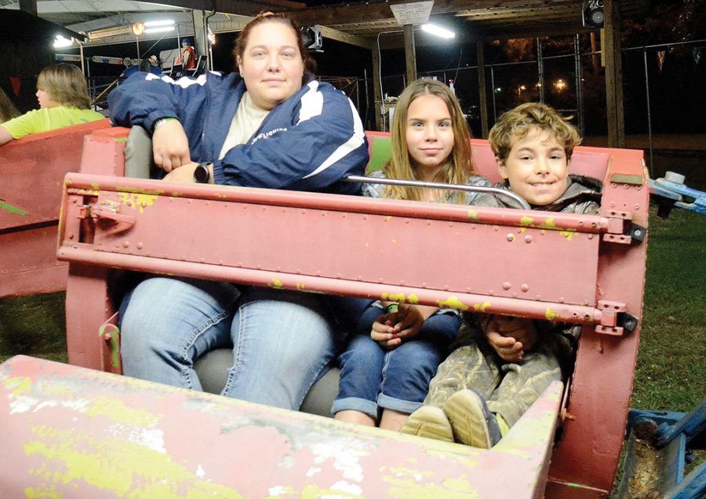 Photo by Aaron Paden/Shirley Dardar (left), Eliza Walley and Joman Lewis wait excitedly for The Scrambler to start at the Log A Load fundraiser Saturday at the Exchange Club Park. The fundraiser raised over $30,000 in one day for the Blair E. Batson Children's Hospital.