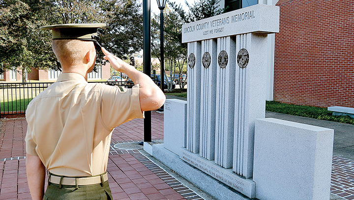 Photo by Donna Campbell/A Marine stops Wednesday at the Lincoln County Veterans Memorial at the Lincoln County Government Complex to salute the members of the armed forces whose names are engraved on the 230 bricks placed in the walkway on either side of the monument.