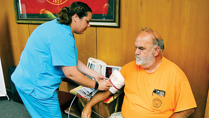 Photo by Donna Campbell/Amy Case, a nurse with King's Daughters Medical Center, checks Billy Case's blood pressure Wednesday during the wellness fair organized for Brookhaven city employees. Billy Case, no relation to Amy Case, works in the city's street department.