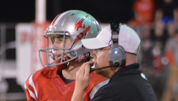 Photo by Lydia King/  Hornets' head coach Adam Cook and Parker Flowers confer during a break in the action against Amite County Friday.