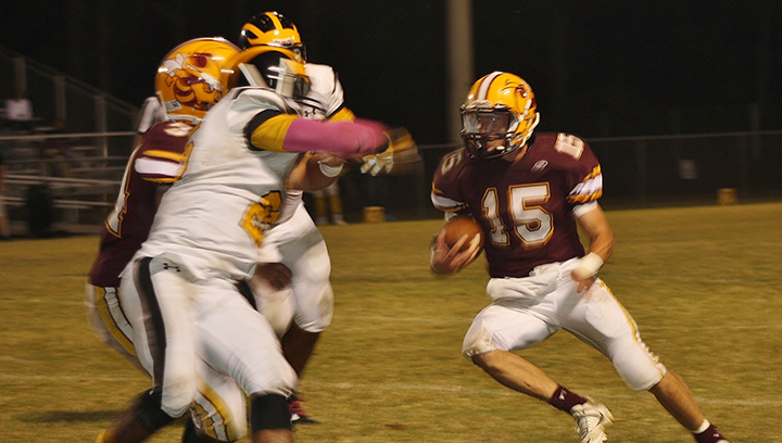 Photo by Christy Boyte/Zach Hodges for the Yellow Jackets (15) attempts to dodge a Trojan defender in Friday's game.