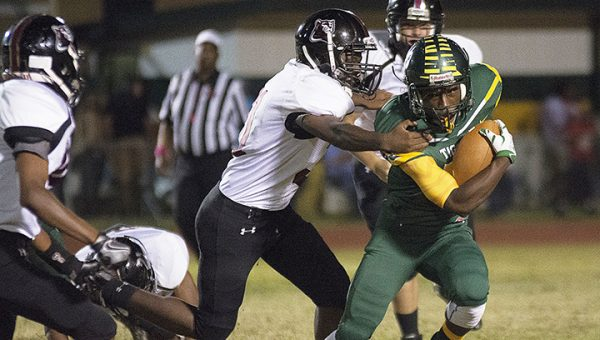 Photo courtesy of the Enterprise-Journal/ A Tiger running back tries to shake off a Cougar defender during Friday night's game in McComb.