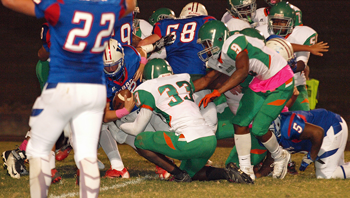 Photo by Tracey Fischer/Cobra quarterback Peyton Burns punches it in for the TD amidst a pile of players.