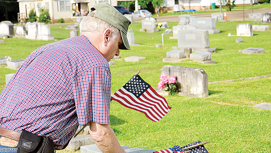 Photo by Donna Campbell/American Legion Post Commander Keith Reeves places American flags at Rosehill Cemetery earlier this year. Volunteers are needed Saturday at 8:30 a.m. at the Rosehill, East Haven, Carver Heights and Hillcrest cemeteries to mark the graves of deceased veterans as a Veterans Day tribute. Volunteers will also be needed the following Saturday at the cemeteries to pick up the flags.