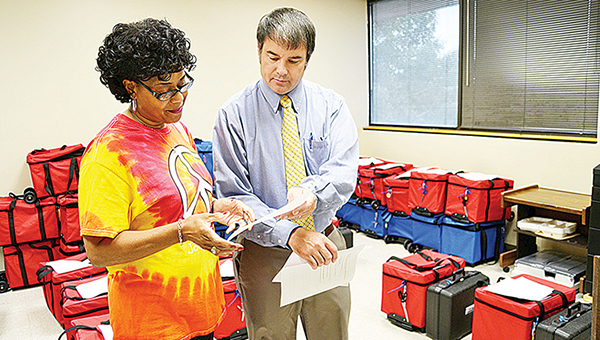 Photo by Donna Campbell/Carolyn Kees, poll manager for the Johnson's Grove precinct, goes over some last minute instructions with Lincoln County Circuit Clerk Dustin Bairfield Monday. Polls are open until 7 p.m. today.