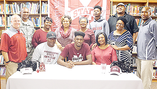 Photo by Jana Harp/Lawrence County power forward KeyShawn Feazell (center) is surrounded by family and his coach Wednesday as he signs with Mississippi State. Lawrence County Athletic Director Cory Keyes said Feazell has racked up many accomplishments while at LCHS, including 2016-2017 Dandy Dozen, 2016 Hot Bed Classic MVP, 2016 MHSAA Region VI District 4A MVP, Rumble in the South MVP, No. 3 player in the state rankings, Powerade All-American Lineage of Champions MVP, ESPN Ranked 45 power forward in the nation, 2015 Nike Elite Top 100 player in nation, 2015 Bay High Christmas Tournament All Tournament, 2015 Super Sophomore selection, 2015 ESPN ranked 29th power forward regional, 2015 and 2016 Lawrence County High Best Offense and 2015 and 2016 Lawrence County High School Glass Eater Award.
