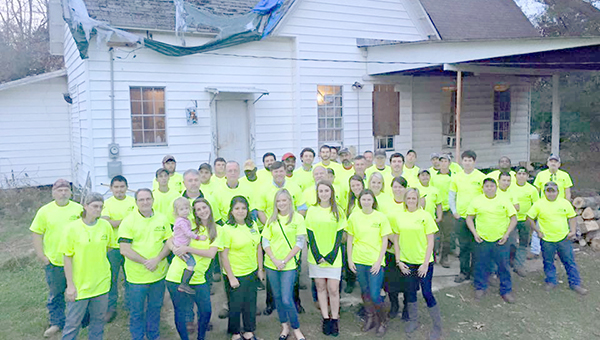 "Photo submitted/Reed's Metals employees gathered at Sara Armstrong's home last year to install a free metal roof. Armstrong was selected as the Lincoln County recipient of the corporation's ""Covering the Community"" project. The company is currently accepting nominations for a family in need of a roof this holiday season at www.reedsmetals.com."