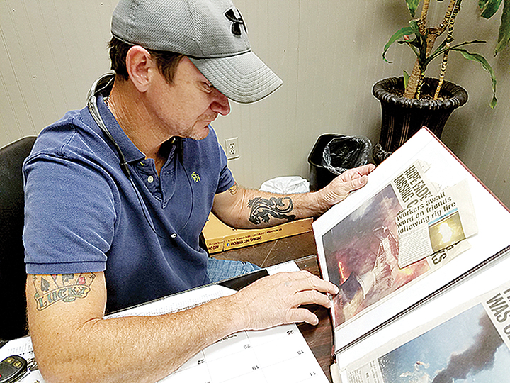 Photo by Donna Campbell/Ken Roberts looks over a scrapbook of news articles he's collected about the Deepwater Horizon explosion. Roberts, of Loyd Star, was one of 126 workers on the oil rig that exploded in 2010.