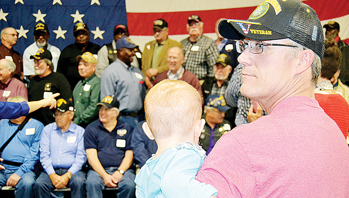 Photo by Donna Campbell/Roy Barnett Jr. holds his granddaughter, 2-year-old Delilah Barnett, while his father gets his group photo taken. Barnett, of East Lincoln, served in the Army in Desert Storm, while Roy Barnett Sr., of West Lincoln, served as a Marine in Vietnam.