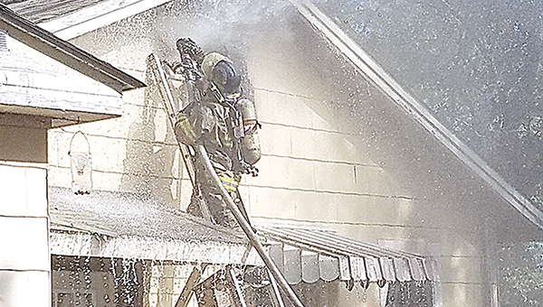 Photo by Donna Campbell/A member of the Brookhaven Fire Department work Monday to put out a fire at a home on East Monticello Street Monday morning.