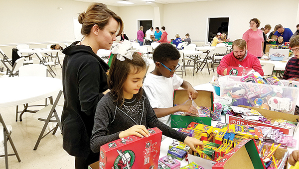 Photo by Donna Campbell/Angi Lins (left) helps Stella Lins and Kaleb Williams pack Operation Christmas Child boxes earlier this week. Aaron King and Cody Barrett, at the end of the table, mark the boxes with the appropriate stickers and seal them for travel.