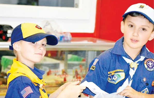 Photo submitted/Hayden Ezell (left) and Ayden Carraway of Cub Scout Troop 125 help prepare donated items for Socks for Heroes to ship to veterans last year.