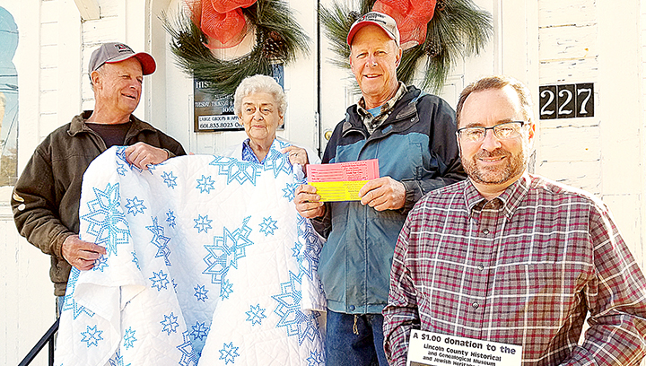 Photo by Donna Campbell/Carroll Montgomery (left), Sue Dorman, Harrell Montgomery and Kevin Laird show off the handmade quilt that will be given away Dec. 4 at the Lincoln County Historical and Genealogical Society's open house. Tickets for the raffle are $1 each and will be sold up until the drawing during the event.