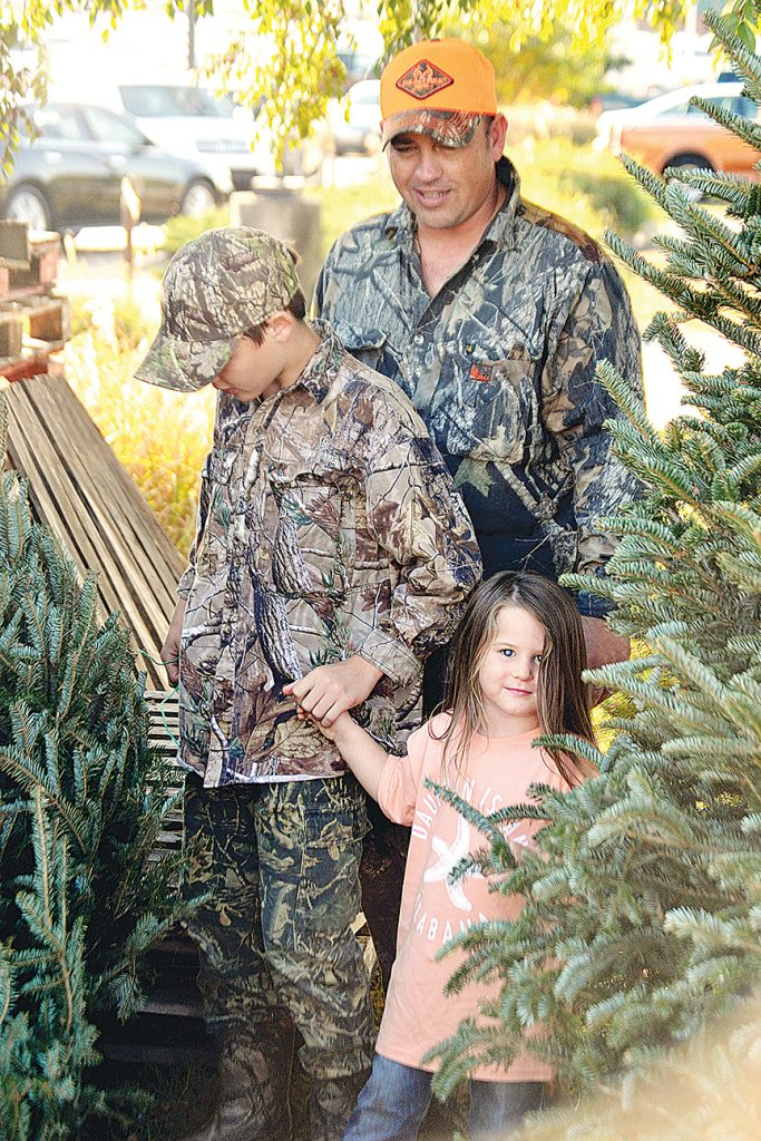Photo by Donna Campbell/After a morning deer hunting, Deacon Wallace, left, shops for a Christmas tree with his dad, Justin Wallace, and sister, Cambri Saturday at Brookway Market Basket. The family, from Bogue Chitto, wanted a live Frazier fir this year and Cabri, who is almost 4, picked one more than double her height.