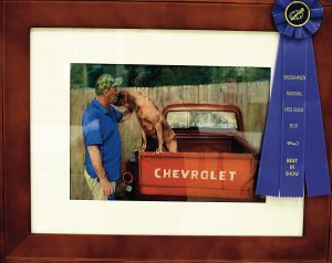 "Gwin Robertson's ""Man and Best Friend"" won Best in Show at BRAG's annual art competition. Robertson, who has been painting since 1988, said she was inspired by the image of her neighbor petting his dog."