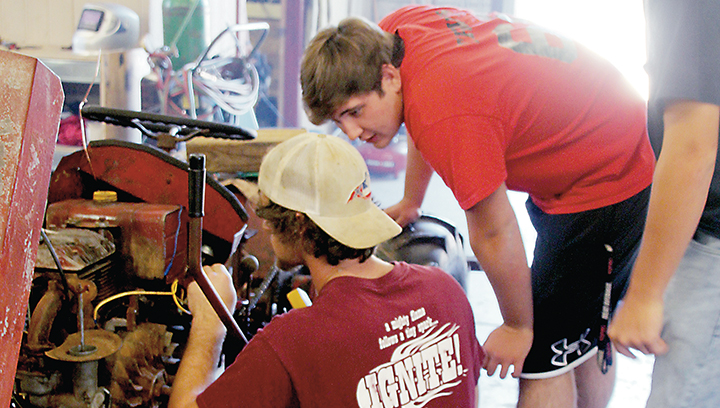 Photo by Alex Jacks/Loyd Star Agriculture Academy students Stewart Thomas (left) and Canon Travis examine a 1920s tractor in the school's shop that they'll restore to its original condition for the owner.