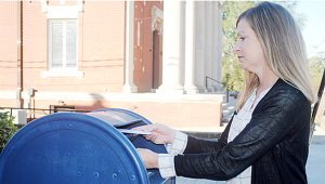 Photo by Aaron Paden/ Laurie Sullivan drops a letter into the post box on West Cherokee Street Thursday. More and more people will be mailing letters, postcards and packages leading up to the Christmas holidays.