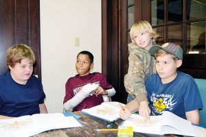 Photo by Donna Campbell/Webelos from Pack 119 Brodee Simpson (left), Camdyn Reeves, Asher Newman and John Kelly Perkins work on their family trees recently at a workshop hosted by the Lincoln County Historical and Genealogical Society.