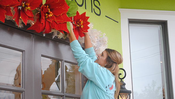 Photo by Aaron Peden/Chasity Furr adjusts some front-door decorations Monday at Expectations, a boutique on Brookway Boulevard, in preparation for Christmas Open House Saturday.