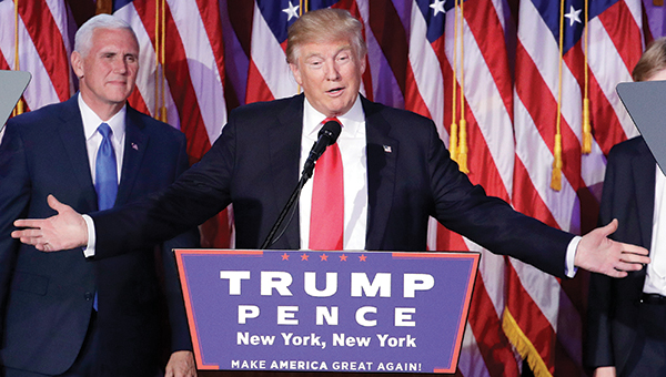 AP Photo by John Locher/President-elect Donald Trump gives his acceptance speech during his election night rally early this morning in New York as running mate Mike Pence looks on.