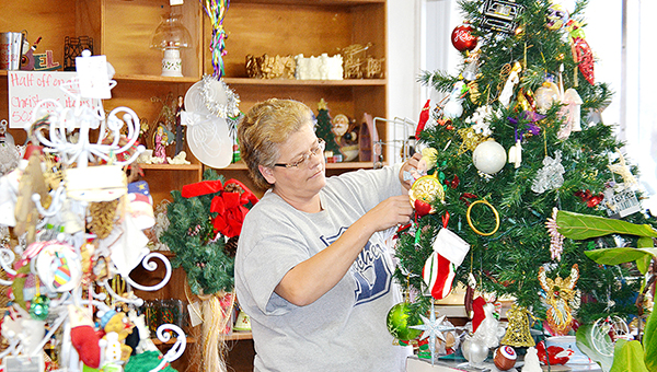 Photo by Donna Campbell/Sandra Rials, assistant manager at the St. Andrew's Thrift Store in Brookhaven, hangs a few ornaments on one of the display Christmas trees. Funds from sales of items at the thrift store helps fund the ministry of St. Andrew's Mission. The store is open Monday-Friday from 9 a.m.-5 p.m. and Saturday 9 a.m.-2 p.m.
