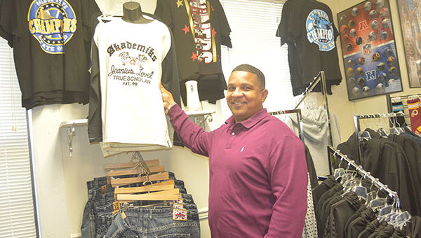 Photo by Orionna BrumfieldBasketball coach-turned-businessman Robert Hines hangs up merchandise in SBS Trends, a clothing store he and his family own in Brookhaven.
