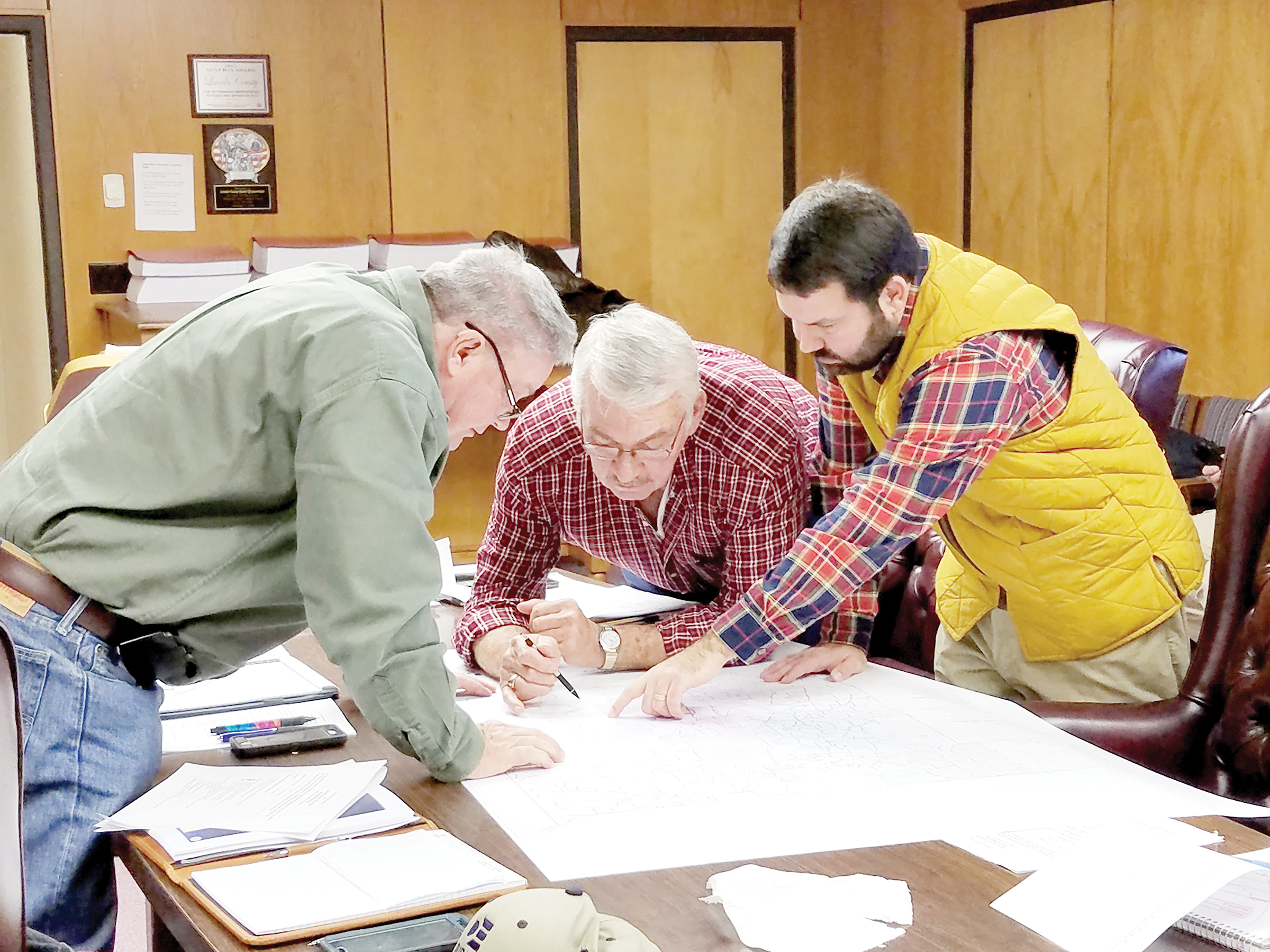 Photo by Donna Campbell/Lincoln County Supervisors Eddie Brown (left) and Nolan Williamson look at a first draft of a county fire district map with county engineer Ryan Holmes.