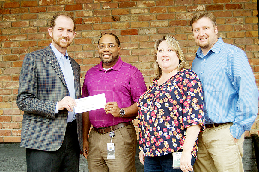 Photo by Donna Campbell/Shaheed Hickman, vice president of distribution at McLane Southern, presents a check for almost $10,000 to Jason Snider with the United Way of Lincoln County (far left) along with Sandy Dussetschleger, expediter, and Jeff Brumfield, controller.