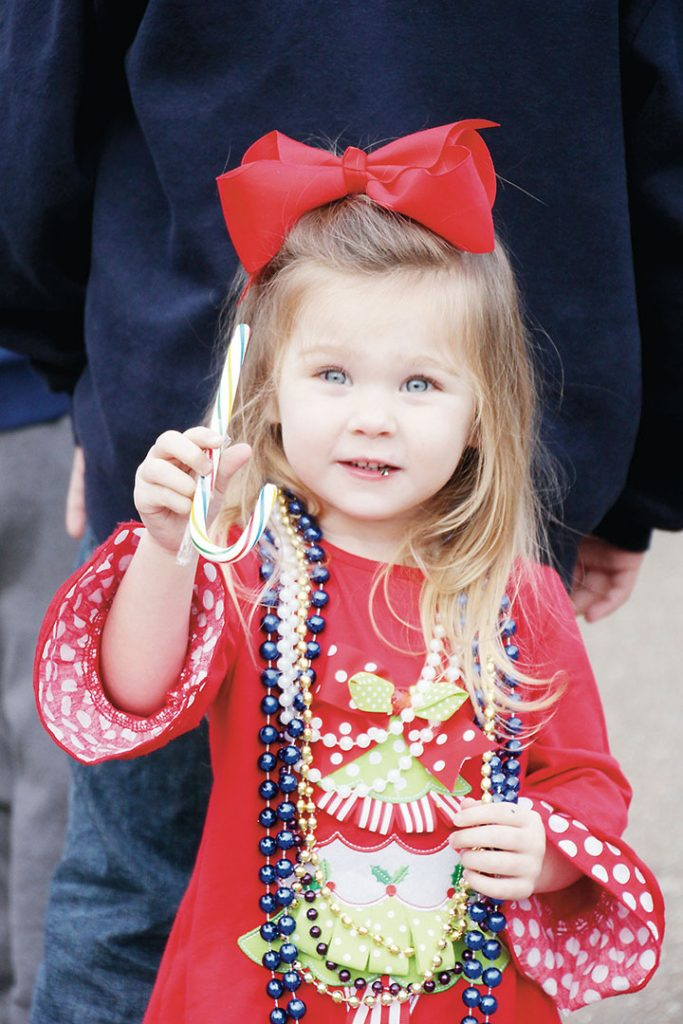 A toddler waits anxiously for Santa while snacking on a candy cane she caught from one of the floats in the 44th annual Wesson Christmas parade. Children of all ages gathered along the streets of downtown Wesson Friday to admire the floats.