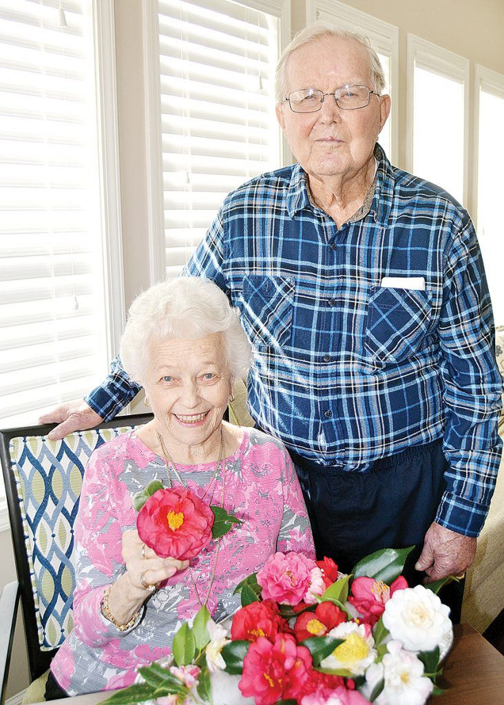 Photo by Donna Campbell/Betty Peters (left) and Frank Burns enjoy the fragrance of fresh-cut camellias in the sunroom at BeeHive Homes in Brookhaven. Peters' late husband, Howard, and Burns' late wife, Kay, will be honored Saturday at the 54th annual Camellia Show hosted by the Brookhaven Camellia Society at the Brookhaven Recreational Center. The event is open to the public after the judging.