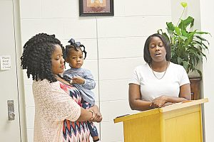 Photo by Donna Campbell/Alicia Leggett, holding her daughter Kinsley Dickey, sings with her sister, Ashley Leggett, at the Brookhaven's First Achievers Black History Month reception Saturday at the Lincoln County Public Library. The exhibit, organized by Maxine Allen and Jennifer Allen-Stenson, spotlights dozens of black Lincoln Countians. It will remain on display throughout the month.